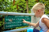 Boy read about Buddhism in the wild at pagoda — Stockfoto