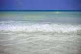 Sea waves in azure water at the blue sky bakcground — Stock Photo
