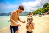 Father adjusting his sons snorkel and mask before swimming — Stock Photo