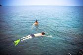 Friends snorkeling in the azure sea near boat — Stock Photo