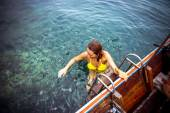 Happy girl at boat in the azure tropical transparent sea looks on strip fish — Stock Photo
