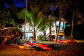 Kayaks lying on the beach near palm trees and house at night — Stock Photo