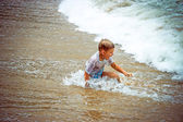 Boy at the sea lying in sand and waves — Photo