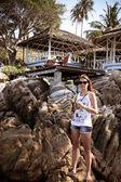 Woman use phone on the stone at beach Koh Samui — Stock Photo
