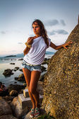 Woman standing near a stone at sunset — Stock Photo