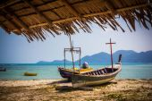Fishing boat could be seen from  palm roof — Stock Photo