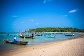Boats on sand beach overlooking island — Stock Photo