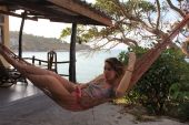 Woman posing at romantic hammock in private house near tropical beach — Stockfoto