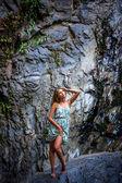 Beautiful girl posing in dress at the waterfall — Stock Photo