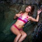 Beautiful sexy model posing in water of waterfalls wearing bikini swimwear at summer time — Stock Photo #60736773