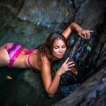 Beautiful sexy model posing in water of waterfalls wearing bikini swimwear at summer time — Stock Photo #60736845
