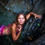 Beautiful sexy model posing in water of waterfalls wearing bikini swimwear at summer time — Stock Photo #60736931