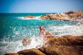 Young sexy woman in red bikini posing In front of sea on the stones and splashes water. Koh Samui beach — Stock Photo