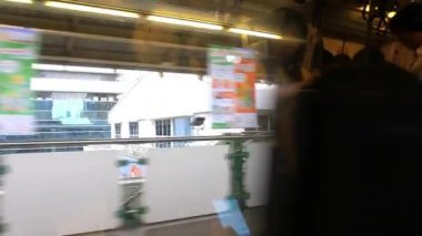 Thailand, Bangkok, 1 August 2014. Looking out the window of moving Bangkok City Skytrain. Reflected in Window Of a people using phone. HD. 1920x1080 — Vídeo stock