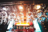 Empty glasses hanging at the bar and Bar with bottles Blurred Background — Stock Photo