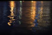 Night landscape, sea, colored lights reflected in water — Stock Photo