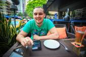 Man sitting at an outdoor cafe table with a phone — Stock Photo