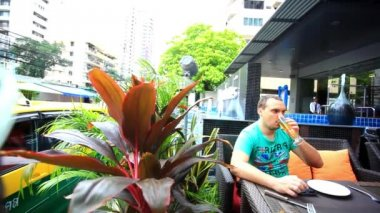 Man sits outdoor at the cafe and using smartphone. HD. 1920x1080 — Stock Video