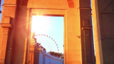 Ferris wheel behind the wall is seen in large aperture during sunset. Moscow. ENEA. HD. 1920x1080 — Stock Video