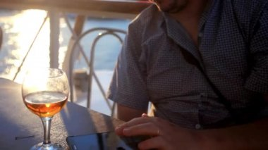 Businessman uses smartphone in sea voyage on cruise ship and drinking glass of wine. Change focus On ripple sunlight water. HD. 1920x1080 — Stock Video