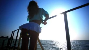 Carefree sexy woman in sunset standing on the pier. View up at ass. HD. 1920x1080 — Stock Video