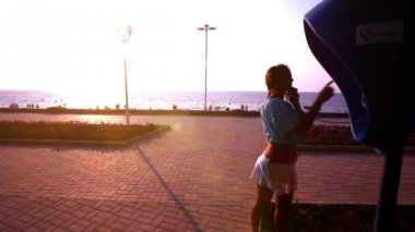 Young woman having a call on public telephone at the beach in sunset. HD. 1920x1080 — Stock Video