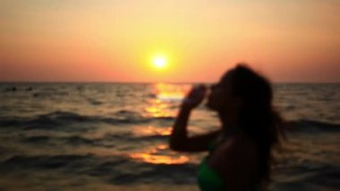 Woman drinking from a Water Bottle at Sunset on the beach. Blurred background. HD. 1920x1080 — Stock Video