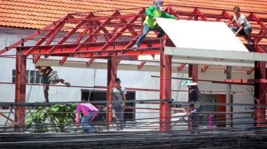 THAILAND, KOH SAMUI, JULY 2, 2014 Construction crew working on the roof sheeting of house at background Of many electric cables. Video — Стоковое видео