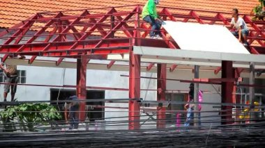THAILAND, KOH SAMUI, JULY 2, 2014 Construction crew working on the roof sheeting of house at background Of many electric cables. Video — Stock Video