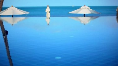 Swimming pool by the sea on background of blue sky near beach and white umbrellas. Video shift motion Koh Samui Thailand — Стоковое видео