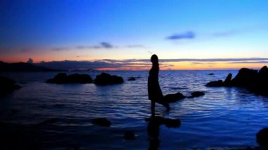 Silhouette of woman walking on a rocky beach during amazing sunset. Romantic video in Thailand Koh Samui — Stock Video
