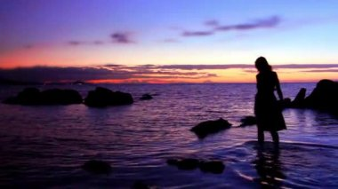 Silhouette of woman walking at a rocky beach, rises on stone against amazing sunset. Romantic video in Thailand Koh Samui — Stock Video
