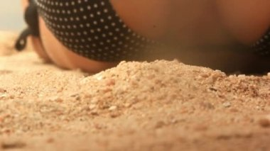 Female sitting on beach wearing bikini sifting sand through her fingers. Close up video — Stock Video