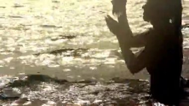 Woman emerges from the sea and drinking water at sunset — Stockvideo