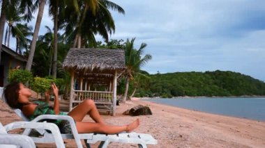 Young  brunette woman lies on sunbed outside in the beach and uses phone. Koh Samui — Stok video