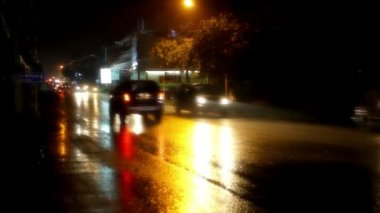 Cars and motorbikes driving on a wet road at night after rain. Video — Stock Video