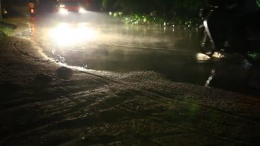 Car and motorbikes drives through a puddle on the road at night after rain. Video — Stock Video