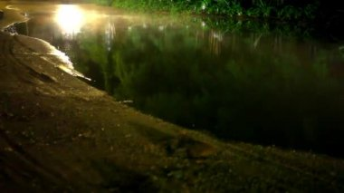 Motorbikes drives through a puddle on the road at night after rain. Video — Stock Video