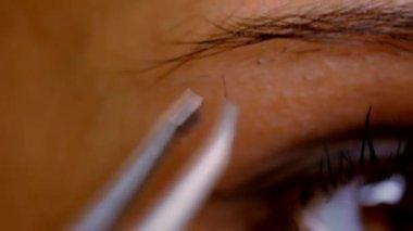 Part of face woman plucking eyebrows depilating with tweezers. Macro video — Stock Video