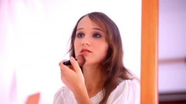 Beautiful young girl paints lips powder preens near the mirror. Video — Stock Video