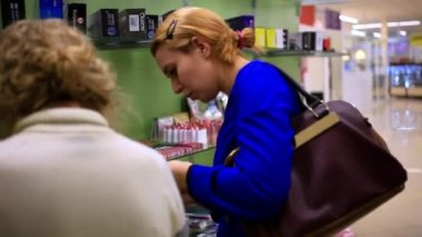 Young blonde woman consults and shopping in the womens cosmetics store, selects some goods. HD. 1920x1080 — Stock Video