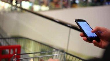 Kontraktlicher Hände mit Telefon in der Shopping-Mall bis gehen Rolltreppe mit Wagen. Hautnah. Hd 1920 x 1080 — Stockvideo