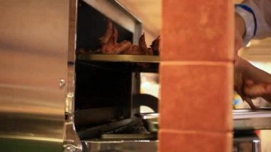 Chef putting meat into oven in the kitchen. HD. 1920x1080 — Stock Video