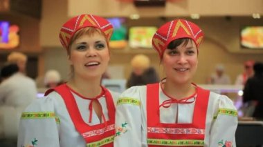 RUSSIA, MOSCOW, 7 MARCH 2015,  Smile young women in russian traditional costume presenting Russian cuisine. Red sarafan and kokoshnik. HD. 1920x1080 — Vídeo stock