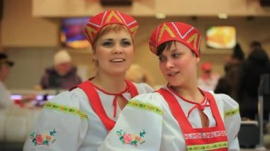 RUSSIA, MOSCOW, 7 MARCH 2015,  Smile young women in russian traditional costume presenting Russian cuisine. Red sarafan and kokoshnik. HD. 1920x1080 — Стоковое видео