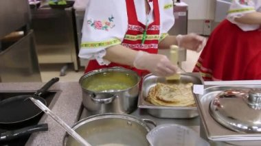 RUSSIA, MOSCOW, 7 MARCH 2015, Young woman chef in russian traditional costume red sarafan and kokoshnik prepares pancakes at the grocery store At kitchen — Vídeo stock