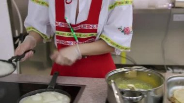 RUSSIA, MOSCOW, 7 MARCH 2015, Young woman chef in russian traditional costume red sarafan and kokoshnik prepares pancakes at the grocery store At kitchen — Стоковое видео