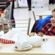 RUSSIA, MOSCOW, 7 MARCH 2015, Woman and son in a supermarket eating some food at the table. Mother shows her son bought food — Stock Video #70387011