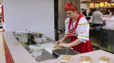 RUSSIA, MOSCOW, 7 MARCH 2015, Woman chef In gloves and russian traditional costume. Red sarafan and kokoshnik packed In a container stuffed pancakes. — Стоковое видео