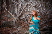 Portrait of a beautiful young woman in turquoise dress standing by trees In jungle forest — Stock Photo